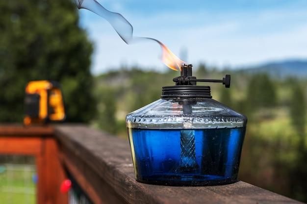 表面に置かれたコンテナと遠くの木々の中で燃える油の選択的なフォーカスショット 無料写真