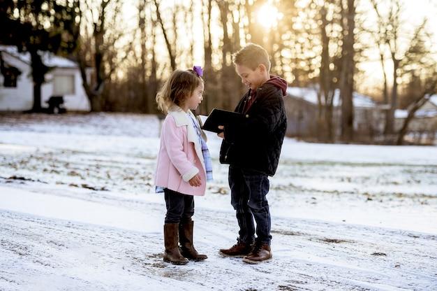 冬の公園の真ん中に聖書を読んでいるかわいい子供たちのセレクティブフォーカスショット 無料写真