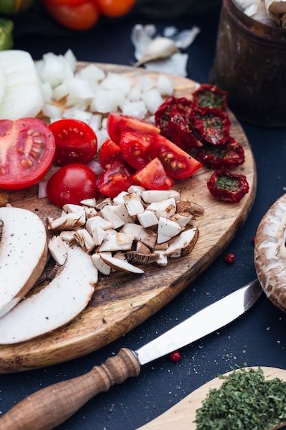 신선한 토마토와 배경을 흐리게 얇게 썬 버섯의 선택적 초점 샷 무료 사진