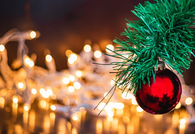 Selective focus shot of a red christmas ball on a pine tree with lights on the background Free Photo