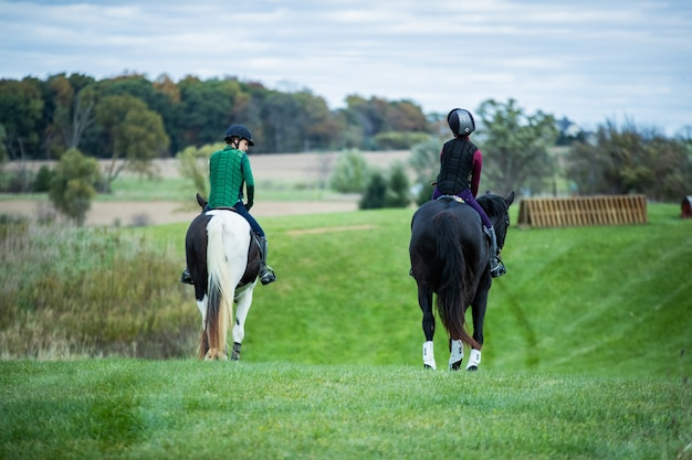 Selective shot of two people wearing horse riding vests riding on horses with black and white tails Free Photo