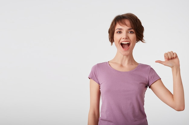 Self assured cheerful short-haired lady in blank t-shirt feels proud of her deeds, points at herself feels surge of pride, raises head, broadly smiles, wears casual clothes, isolated over white wall. Free Photo