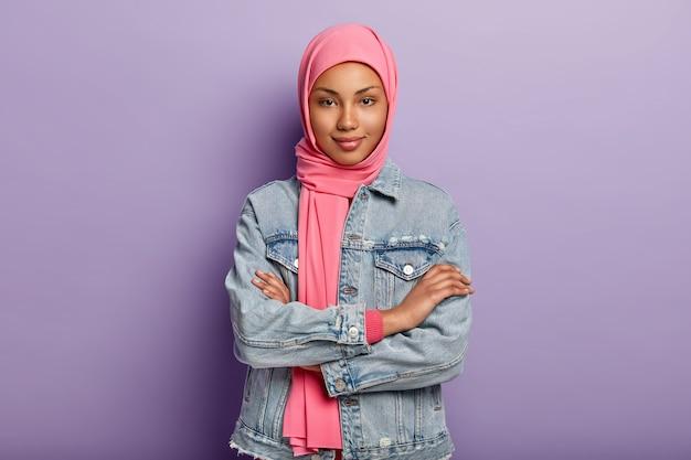 Уверенная в себе темнокожая женщина исповедует мусульманские религиозные взгляды, скрещивает руки, носит розовый платок и джинсовое пальто, изолирована за фиолетовой стеной, с интересом слушает новости Бесплатные Фотографии