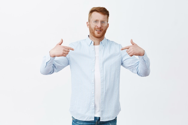 Self-assured proud redhead male entrepreneur in shirt over t-shirt pointing at himself and staring with pride, bragging about own achievements, feeling confident over gray wall Free Photo