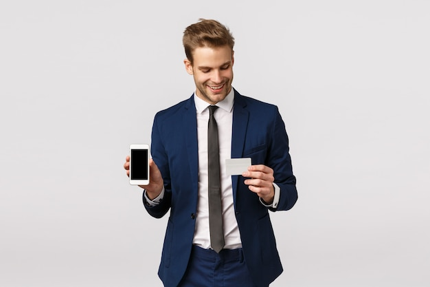 Self-assured young blond businessman in blue classic suit, holding smartphone and credit card, showing mobile display, online payment method, finance application, standing white background Premium Photo