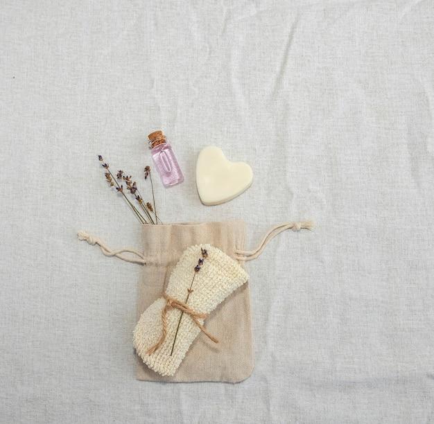 제로-웨스트 컨셉의 셀프 케어 액세서리. 린넨 원단, 린넨 백, 라벤더 향 주머니, 수제 하트 모양 비누 및 라벤더 에센셜 오일. 프리미엄 사진