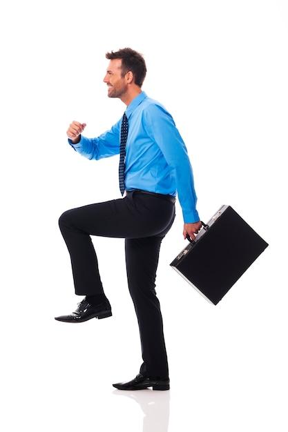 Self confident businessman climbing for success Free Photo