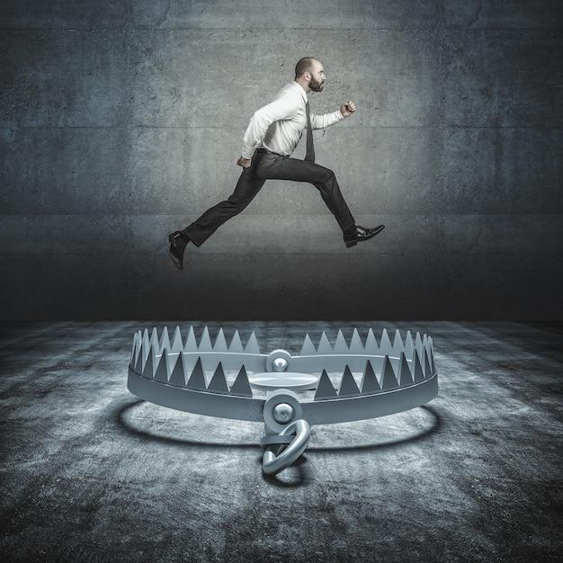 Самоуверенный бизнесмен прыгает в большую медвежью ловушку. концепция преодоления проблем и невзгод. Premium Фотографии