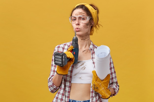 Self-confident female builder wearing goggles, white top and checkered shirt, protective gloves holding drill and papers being dirty after hard work isolated over yellow wall. maintenance Free Photo
