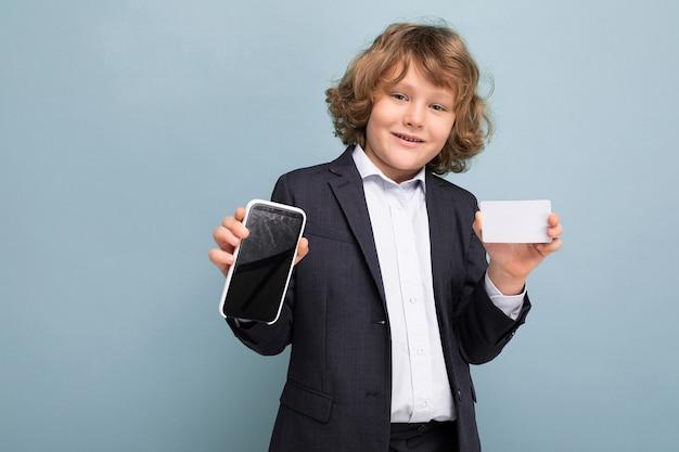 電話とクレジットカードを保持しているスーツを着て巻き毛の自信を持ってハンサムなポジティブ幸せな少年 Premium写真
