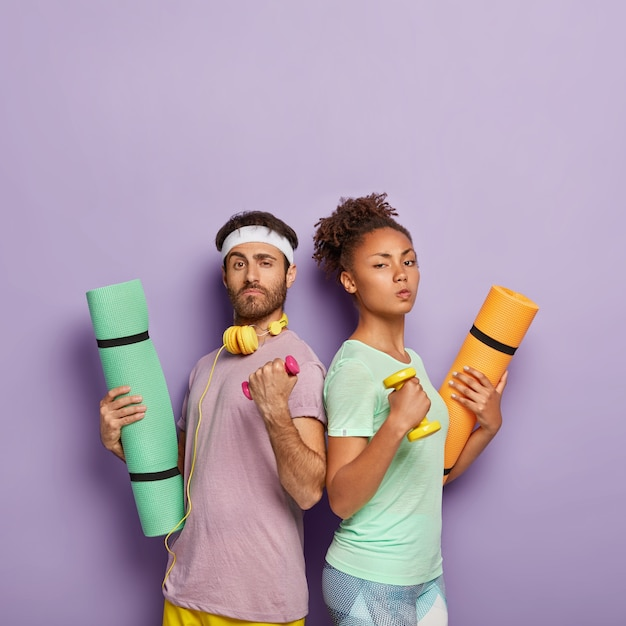 Self confident serious diverse woman and man stand back to each other, raise arms with dumbbells, hold karemats, show their strength, being in good physical shape, isolated on purple wall Free Photo