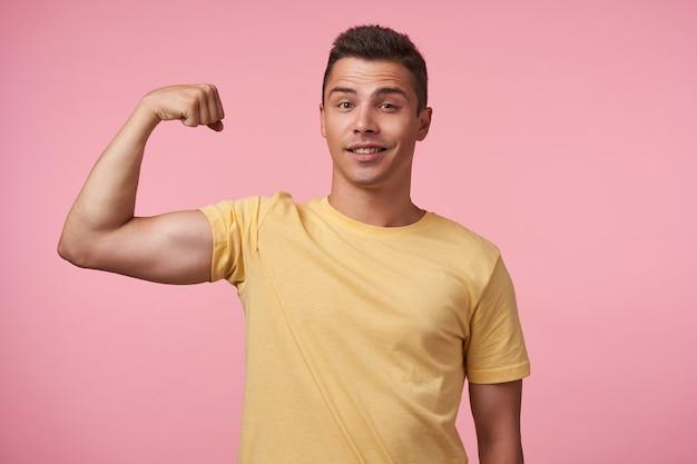 Ragazzo brunetta dai capelli corti e giovane, sicuro di sé, che tiene la mano alzata mentre mostra il suo potere e guarda glaldy alla macchina fotografica, isolato sopra fondo rosa Foto Gratuite