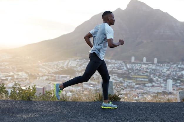 自己決定の暗い肌のスポーティな男性ランナーは、スポーツ服を着て、山道を遠距離恋愛し、新鮮な空気を楽しみ、エネルギッシュでやる気を感じます。人、ライフスタイル、スポーツのコンセプト 無料写真