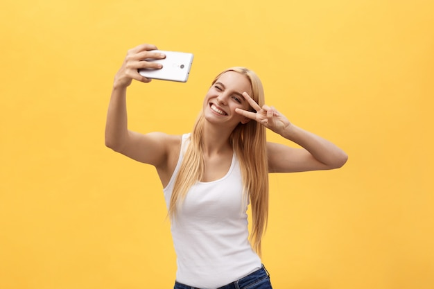 Self portrait of charming cheerful girl shooting selfie on front camera gesturing v-sign peace symbol Premium Photo