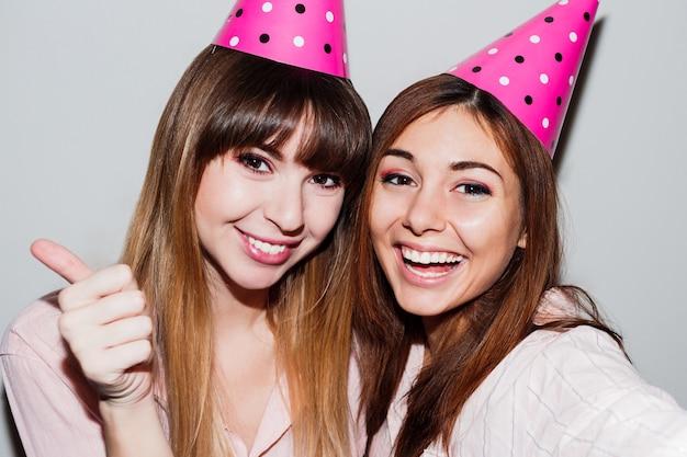 ピンクの紙の誕生日帽子の2人の女性のセルフポートレート。ピンクのパジャマを着ている友人 無料写真