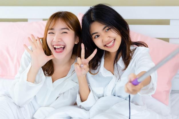 ベッドの上でselfieとうれしそうな10代の親友 無料写真