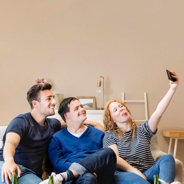 自宅で、selfieを取って3人の友人のグループ 無料写真