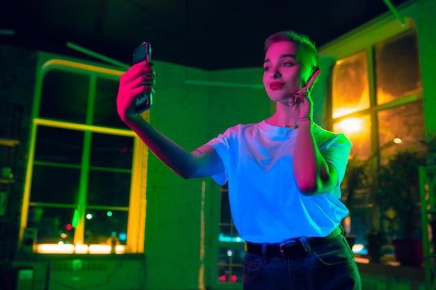 Autoscatto. ritratto cinematografico di donna alla moda in interni illuminati al neon. tonica come effetti cinematografici, colori luminosi al neon. modello caucasico utilizza lo smartphone in luci colorate al chiuso. cultura giovanile. Foto Gratuite