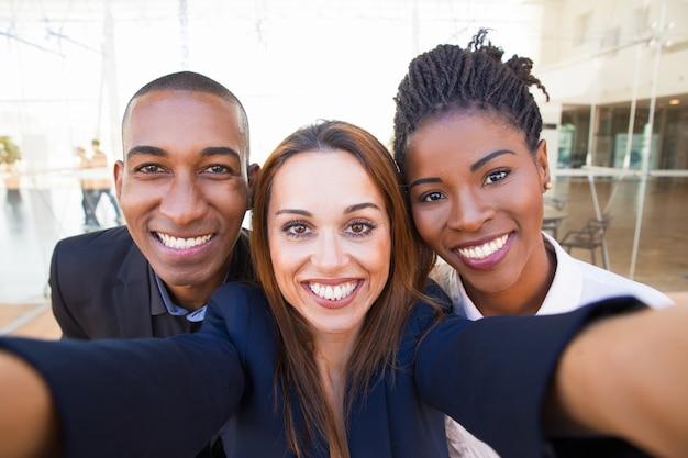 Selfie of happy beautiful intercultural business friends Free Photo