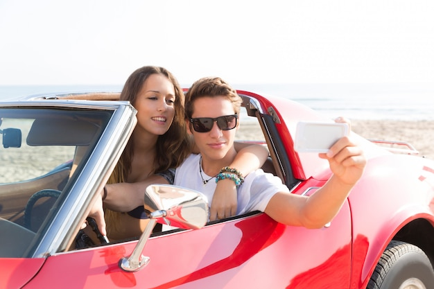 Selfie photo of young teen couple in convertible Premium Photo