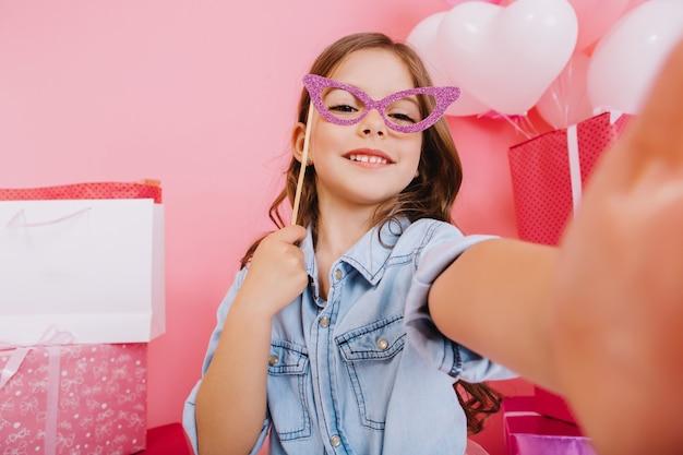 Ritratto di selfie incredibile bambina con maschera viola sul viso che sorride alla telecamera su sfondo rosa. celebrando buon compleanno, palloncini colorati con grandi scatole regalo, esprimendo positività Foto Gratuite