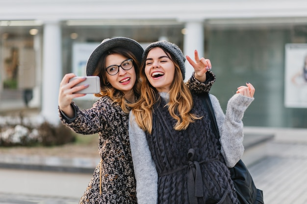 Selfie portrait of joyful fashionable women having fun on sunny street in city. stylish look, having fun, travelling with friends, smiling, expressing true positive emotions. Free Photo