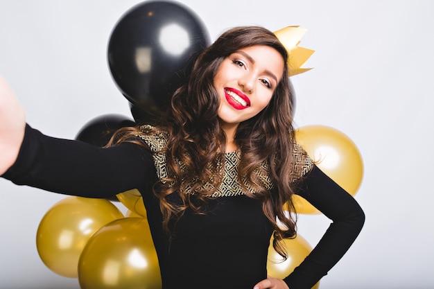 Selfie ritratto gioiosa donna con lunghi capelli ricci bruna, corona gialla, abito nero di lusso. celebrare il nuovo anno, festa di compleanno, divertirsi con palloncini d'oro e neri. Foto Gratuite