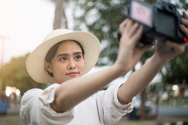 Selfieの肖像画旅行アジア女性のライブストリームで話しているタイの休暇vloggingアジア観光客の女の子のカメラでビデオvlogを記録します。夏の観光地 Premium写真