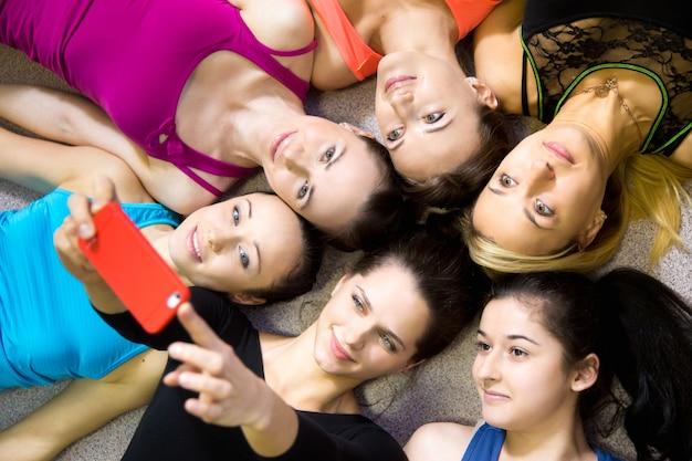 美しいスポーティーなガールフレンドのグループ、selfie、self-portraitをスマートフォンから見たもの 無料写真