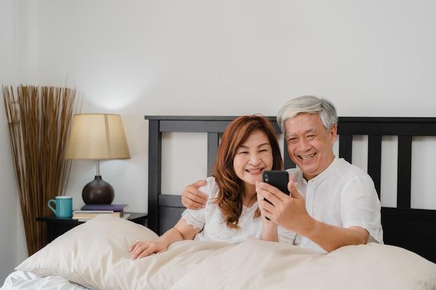自宅でアジアシニアカップルselfie。アジアのシニア中国の祖父母、夫と妻の朝のコンセプトで自宅の寝室のベッドに横になって目を覚ます後携帯電話selfieを使用して幸せ。 無料写真