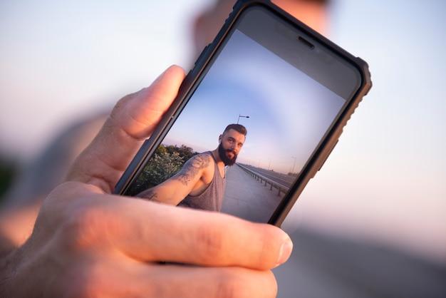 屋外トレーニング中にスマートフォンで自分撮り Premium写真