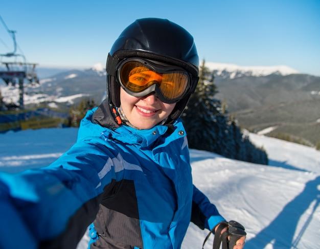 晴れた冬の美しい日にスキーリゾートの山でスキーをした後、斜面で休んでいる間、selfieを取って、笑顔の幸せな女性スキーヤーのクローズアップの肖像画 Premium写真