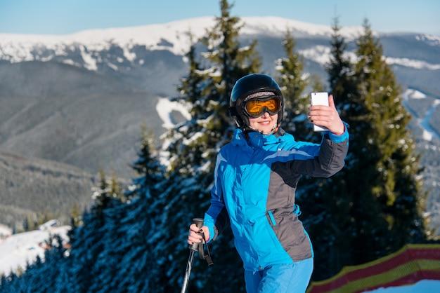 晴れた冬の日にスキーリゾートで山でスキーをしながら彼女のスマートフォンでselfieを取って笑っている女性スキーヤーのショットを閉じる Premium写真