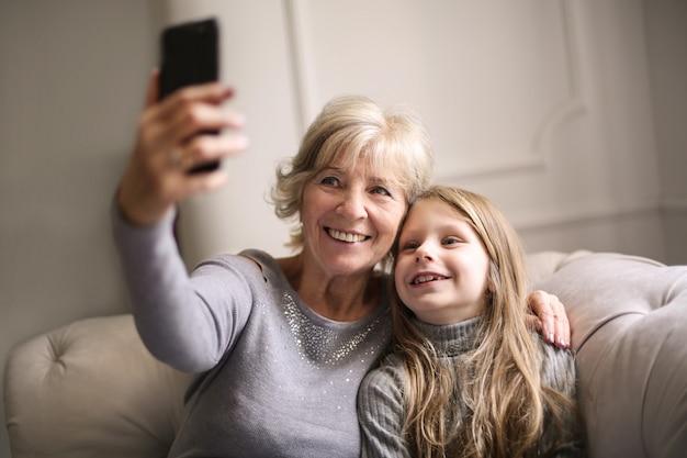 おばあちゃんと孫娘、selfieを取って Premium写真