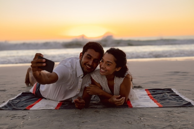 ビーチで携帯電話でカップル撮影selfie 無料写真