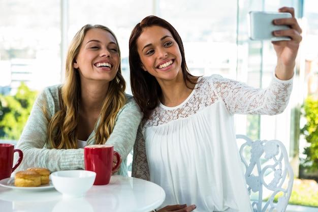 お茶を飲んでいる間二人の女の子がselfieを取る Premium写真