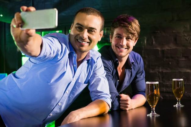 二人の男がバーのカウンターでビールを飲みながら携帯電話でselfieを取る Premium写真