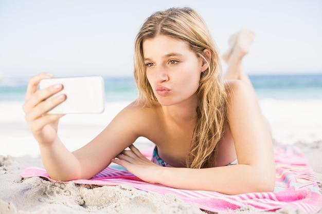 携帯電話でselfieを取る若い女性 Premium写真