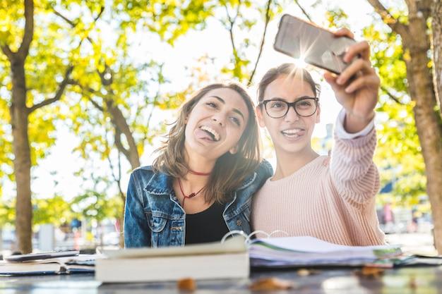 勉強して公園で面白いselfieを取っている女の子 Premium写真