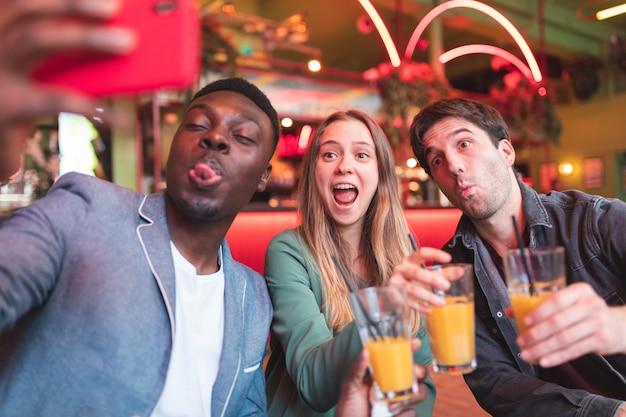 バーで楽しんで、selfieを取って幸せな友達 Premium写真