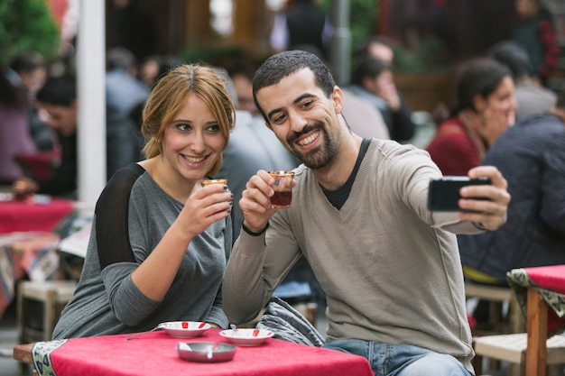 伝統的なお茶を飲みながらトルコのカップル撮影selfie Premium写真