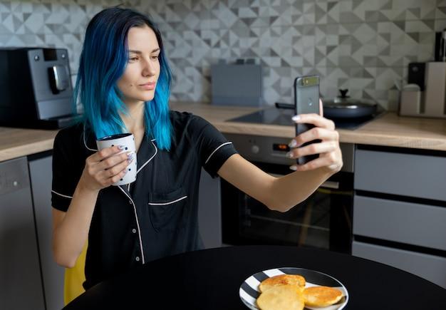 モダンなキッチンでselfieを取って美しい美しい若い女性 Premium写真