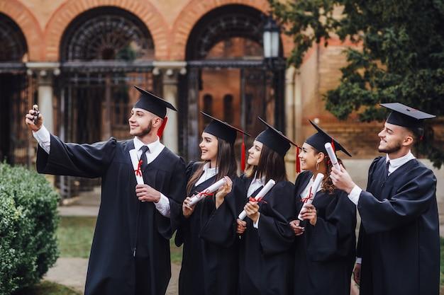 一緒に勉強します。キャンパスに立って、selfieを作る学生のグループ Premium写真