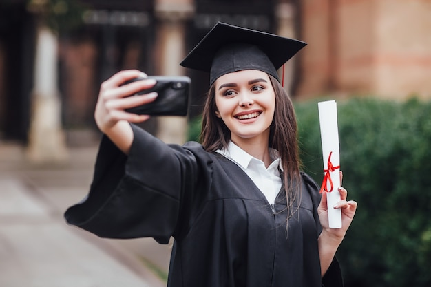 卒業帽子とガウンで卒業した女性は、屋外で共同selfieを作ります。 Premium写真