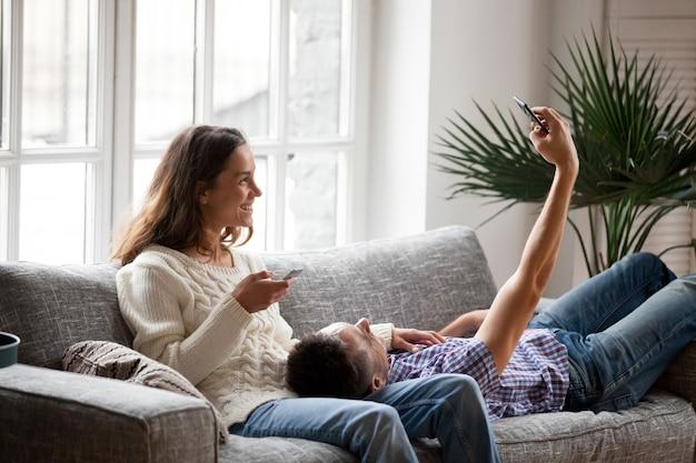 若いカップルが自宅でselfieを取ってスマートフォンを楽しんで 無料写真
