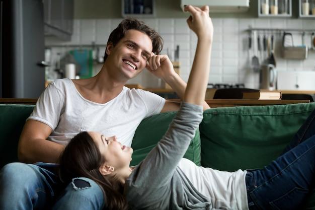 笑顔のカップルが自宅でselfieを取ってスマートフォンを楽しんで 無料写真