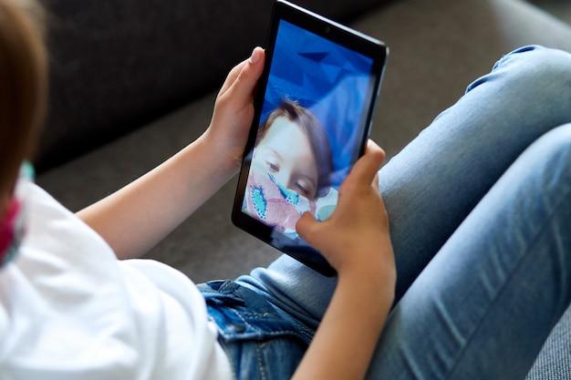 Selfieまたはリモート通信を取るスマートフォンを持つ少女。 Premium写真
