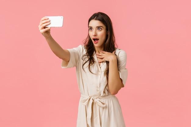 電話でのビデオ通話でガールフレンドと話していると、魅惑的で驚きの表情を作る少女。魅力的なブルネットの女性のドレス、selfieを取って、あえぎ口をあえぎ、面白がって、ピンクの壁に立っています。 Premium写真