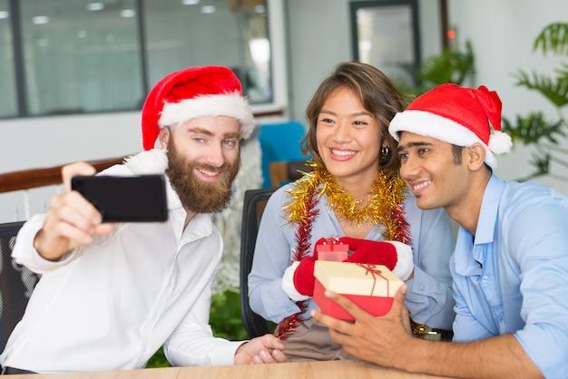 陽気な事業チームのクリスマスselfieを引き継ぐ 無料写真