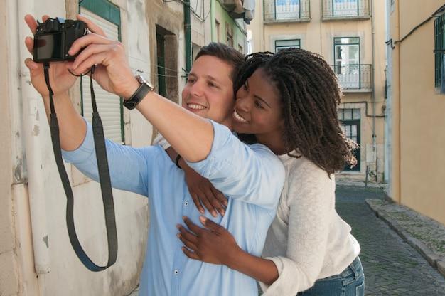 通りでselfie写真を撮る幸せな異人種間のカップル 無料写真